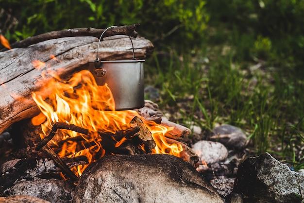Bouilloire suspendue au-dessus du feu.