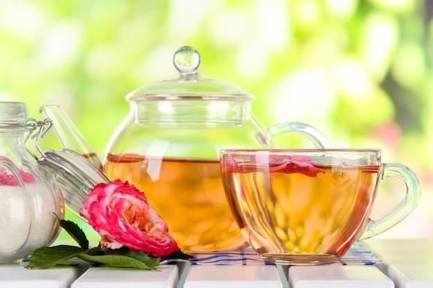 Bouilloire et tasse de thé de thé rose sur serviette sur table en bois sur la surface de la nature