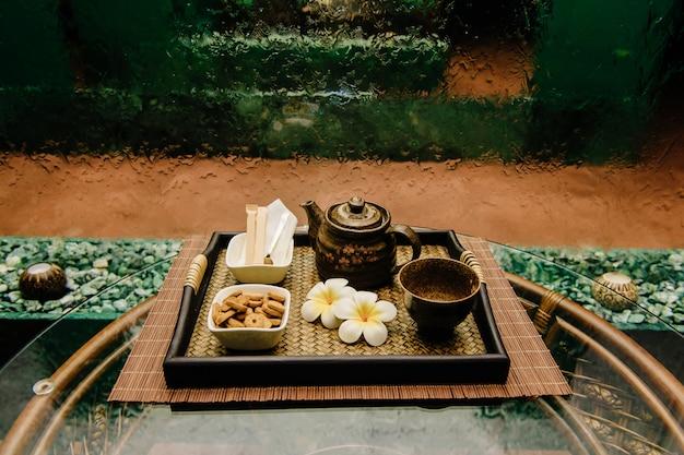 Bouilloire à thé en bronze antique en bronze sur un plateau en osier avec des fleurs de lotus