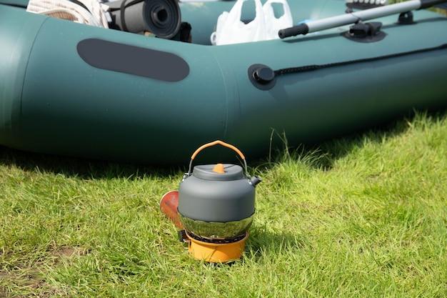 Bouilloire touristique sur un brûleur à gaz. cuisiner dans des conditions de terrain. utilisation d'un brûleur à gaz touristique
