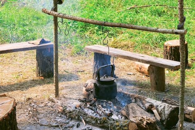 Bouilloire touristique fumée sur feu de camp