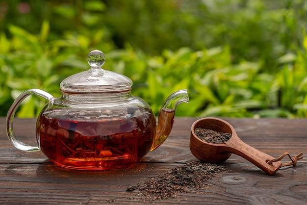 Bouilloire vapeur en verre cuillère en bambou avec thé table en bois brunch pique-nique en plein air