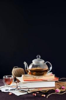 Bouilloire en verre avec du thé noir sur des livres vintage avec tasse et verres, selective focus