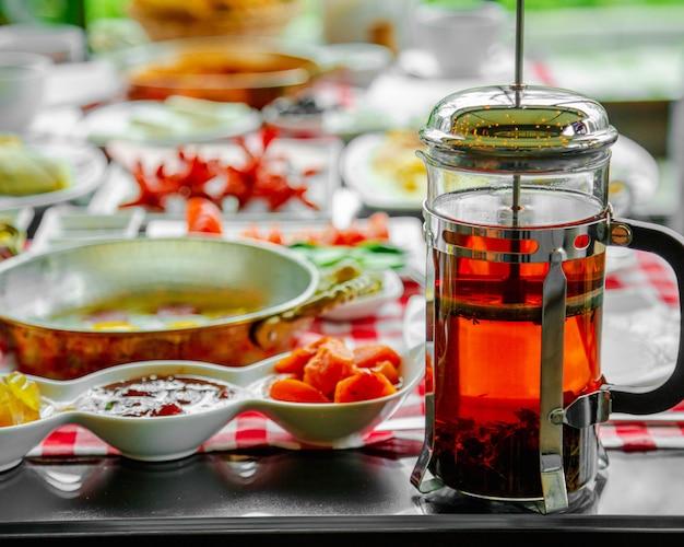 Bouilloire en verre avec du thé noir sur une table de petit déjeuner.