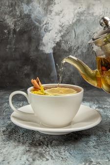 Bouilloire de vue frotn avec thé versant dans une tasse sur la surface sombre matin cérémonie du thé