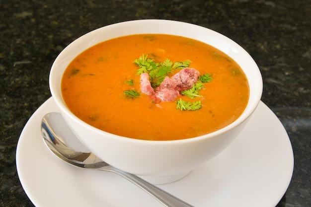 Bouillon de boeuf aux saucisses servi dans un bol blanc prêt à être dégusté.