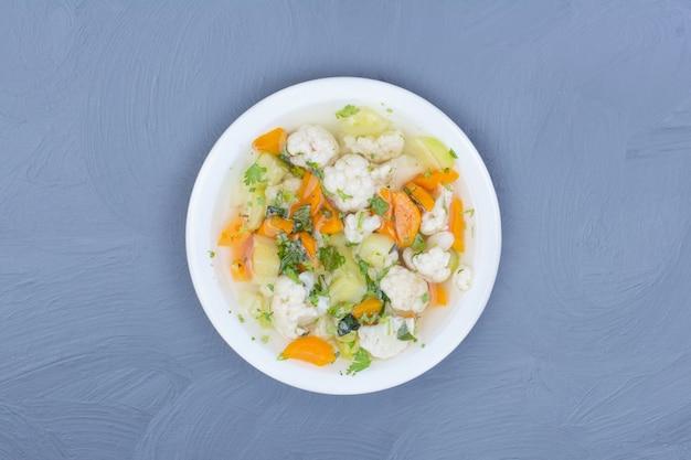 Bouillon de soupe aux légumes hachés et émincés dans une assiette blanche.