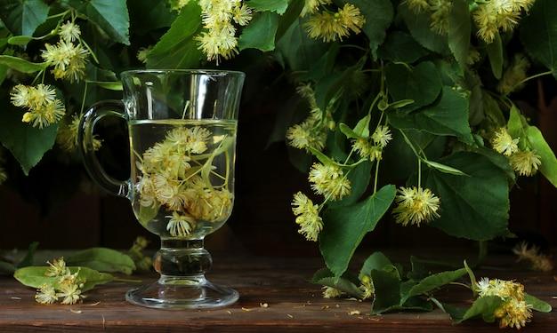 Bouillon de tilleul dans un verre. fleurs de tilleul sur les branches.