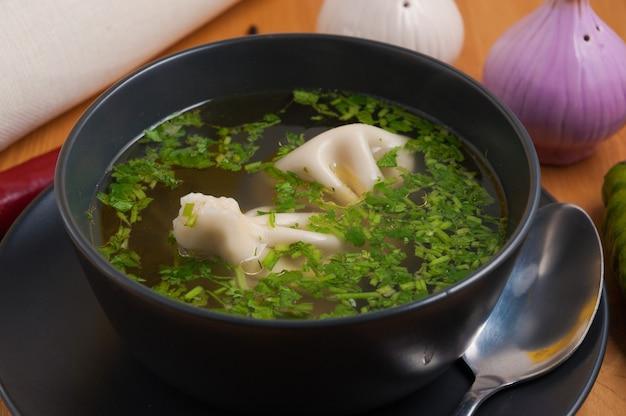 Bouillon de viande savoureux avec khinkali et herbes