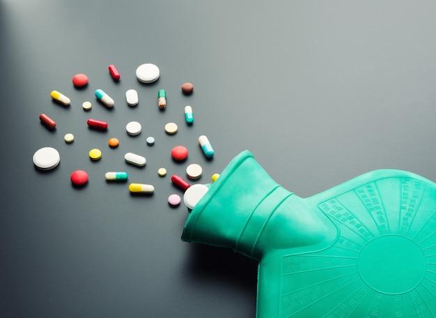 Bouillotte en caoutchouc vert avec des pilules sur fond gris