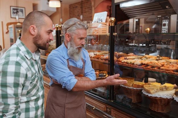 Boulanger âgé aidant son client à choisir la pâtisserie de l'affichage au détail