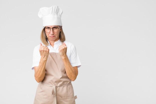 Boulanger d'âge moyen à la femme confiante, en colère, forte et agressive, avec les poings prêts à se battre en position de boxe sur le mur
