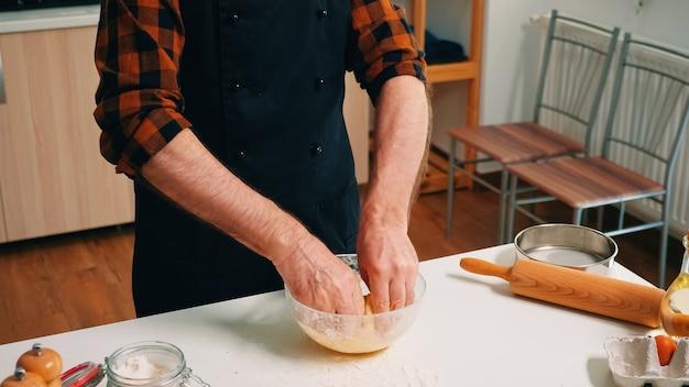 Boulanger âgé avec tablier de cuisine ajoutant de la farine sur la pâte dans un bol en verre. chef âgé à la retraite avec saupoudrage uniforme, tamisage, tamisage des ingrédients bruts à la main et mélange pour la cuisson de pizzas maison, de pain.