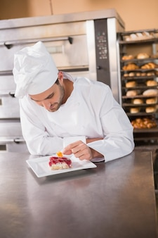 Boulanger concentré mettant des fleurs sur la pâte avec des fruits