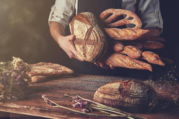 Boulanger avec du pain à la main et une table brune en bois avec des fleurs sèches sur fond noir, photo tonifiée
