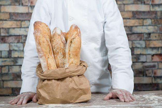 Boulanger avec du pain traditionnel français baguettes