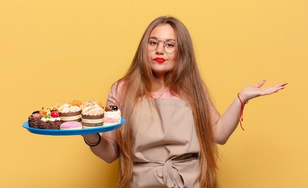 Boulanger d'expression confus de jeune jolie femme avec des petits gâteaux