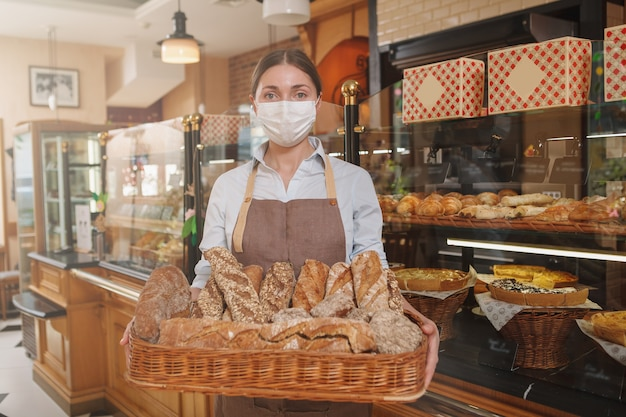 Boulanger femelle portant un masque médical, tenant un panier plein de pain frais
