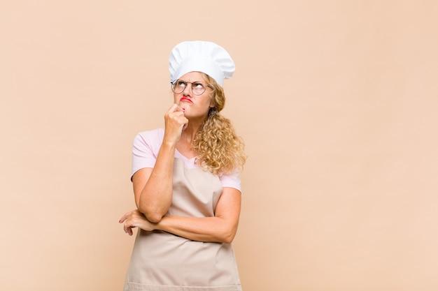 Boulanger de femme d'âge moyen pensant, se sentant douteux et confus, avec différentes options, se demandant quelle décision prendre