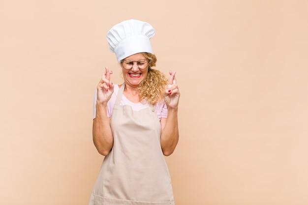 Boulanger de femme d'âge moyen se sentir nerveux et plein d'espoir, croiser les doigts, prier et espérer bonne chance