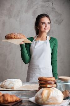 Boulanger de jeune femme heureuse debout et tenant du pain.