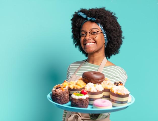 Boulanger de jeune jolie femme afro avec des gâteaux