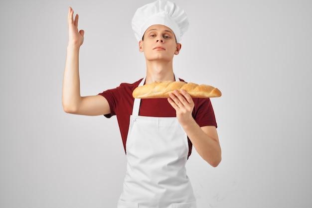 Boulanger mâle dans un tablier blanc tenant un pain à la main la cuisson des aliments