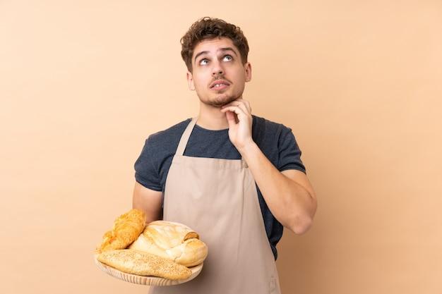 Boulanger mâle tenant une table avec plusieurs pains sur beige en pensant à une idée