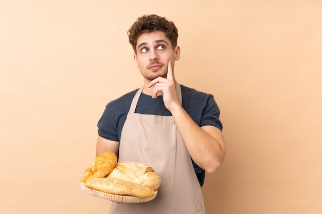 Boulanger mâle tenant une table avec plusieurs pains isolé sur mur beige en pensant à une idée