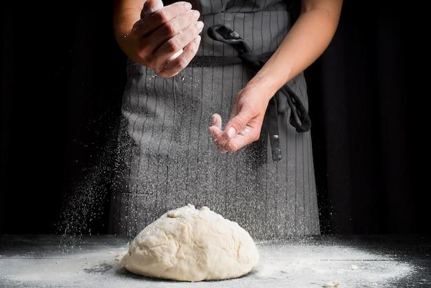 Boulanger à mi-cuisson, verser la farine sur la pâte