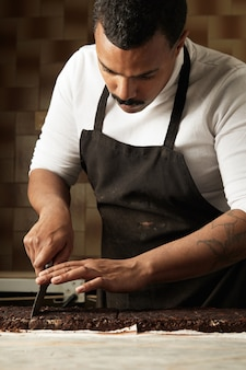 Boulanger noir professionnel sérieux coupé morceau de chocolat biologique fait maison avec des noix et des fruits dans son laboratoire vintage artisanal, sur table en marbre