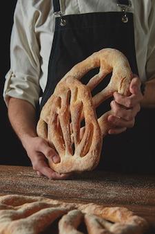 Le boulanger de pain fraîchement délicieux tient dans les mains sur un fond sombre