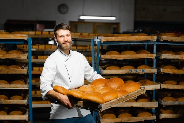 Un boulanger tient un plateau avec du pain chaud frais dans ses mains