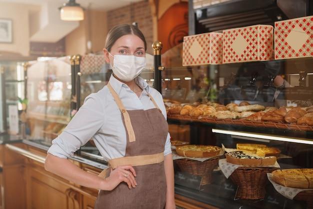 Une boulangère portant un masque médical, travaillant dans sa boulangerie pendant la quarantaine du coronavirus