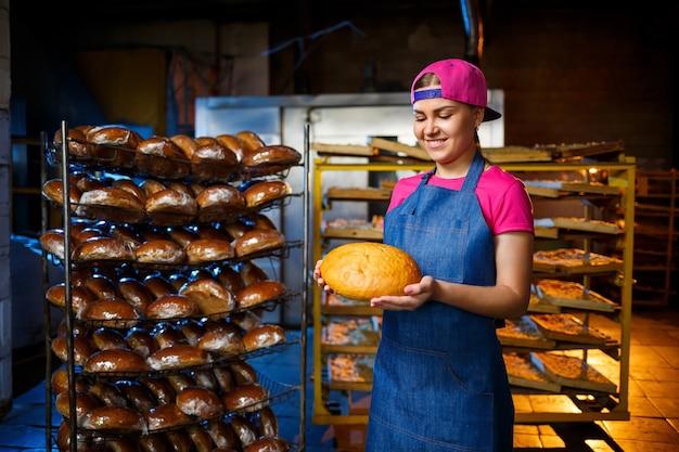 Une boulangère prend du pain chaud dans une boulangerie sur fond de rayonnage avec du pain. production industrielle de pain. l'étape de la cuisson dans une boulangerie