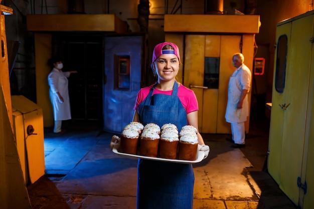 Une boulangère tient un plateau de pâtisseries chaudes à la boulangerie. fabrication de produits de boulangerie. un plateau de pâtisseries fraîches croustillantes.