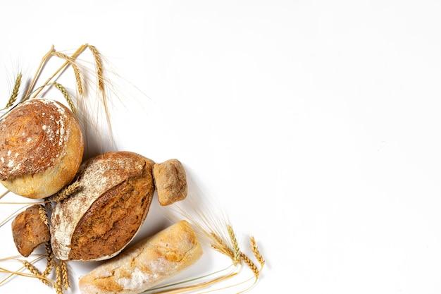 Boulangerie. ensemble de pain et petits pains croustillants fraîchement cuits avec des épis de blé sur fond blanc avec espace de copie, vue de dessus à plat