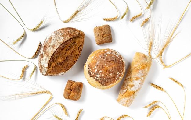 Boulangerie. ensemble de pain et petits pains croustillants fraîchement cuits avec des épis de blé sur fond blanc vue de dessus, mise à plat