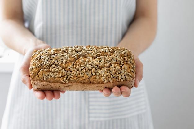 Boulangerie européenne tenant du pain de sarrasin femme blanche dans un tablier léger tenant du levain fait maison