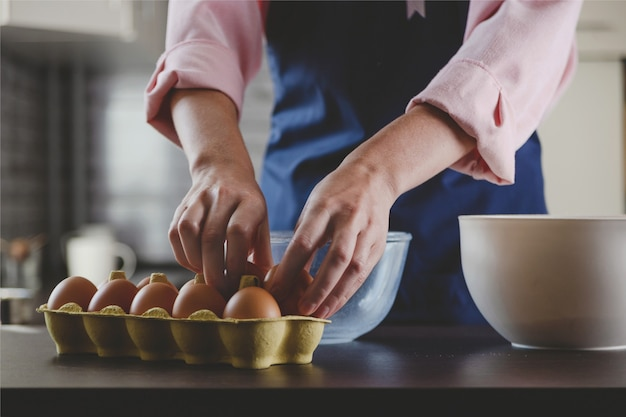 Boulangerie femme en tablier bleu prenant des œufs pour cuisiner à la maison une esthétique de cuisine confortable