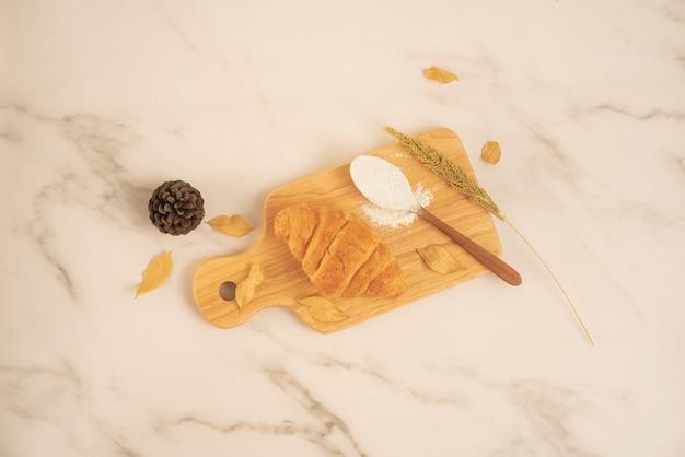 Boulangerie fraîche, croissant frais avec cuillère pleine de farine sur planche de bois sur une surface en marbre blanc. délicieux délicieux dessert, petit déjeuner français. vue de dessus