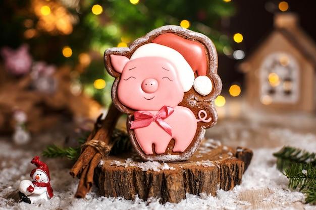 Boulangerie traditionnelle de vacances. cochon rose heureux en pain d'épice au chapeau de noël dans une décoration chaleureuse avec des lumières de guirlande