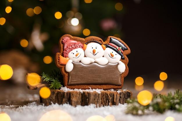 Boulangerie traditionnelle de vacances. trois bonhommes de neige en pain d'épice à la décoration chaleureuse et confortable avec des guirlandes