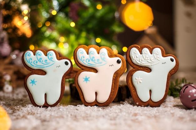 Boulangerie traditionnelle de vacances. trois cerfs de noël blancs en pain d'épice à la décoration chaleureuse et confortable avec des guirlandes