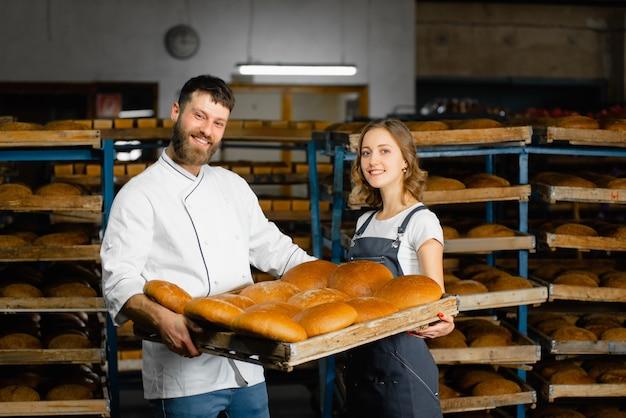 Boulangers à la boulangerie. un homme et une femme tiennent un plateau avec du pain chaud frais