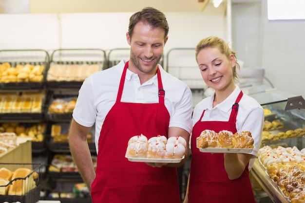 Boulangers souriants ayant une pâtisserie