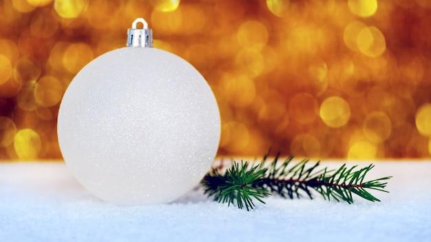Boule blanche de noël avec une branche d'épinette dans la neige sur un arrière-plan flou avec bokeh