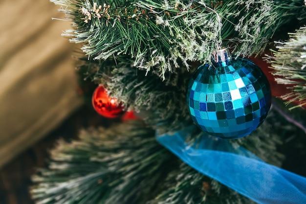 Une boule bleue accrochée à un arbre de noël artificiel