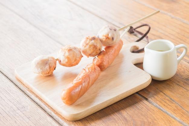 Boule de calmar et hot-dog grillé sur plaque de bois