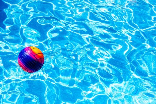 Boule colorée flottant sur une piscine.